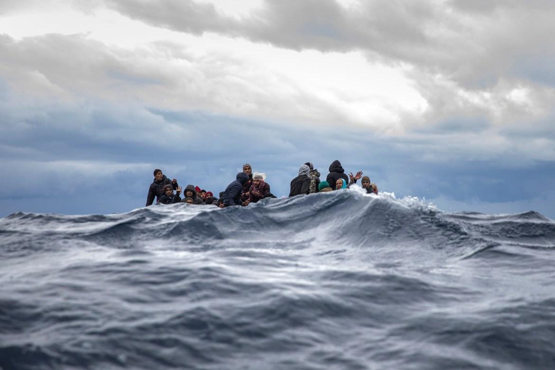 Migranti iz Maroka i Bangladeša čekaju na prepunom drvenom čamcu pomoć pripadnika španske grupe za potragu i spasilačke grupe Open Arms kod libijske obale. (AP)