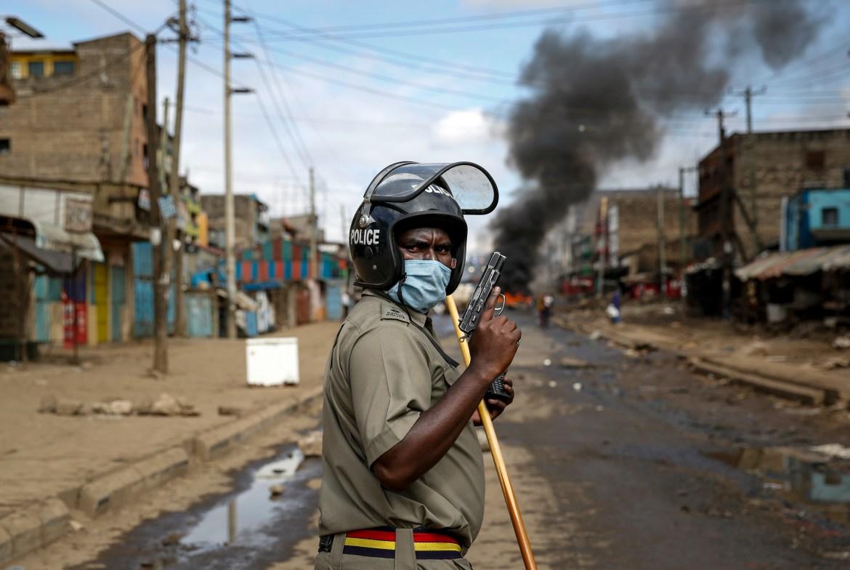 Policajac drži pištolj tokom sukoba sa demonstrantima kod barikada od zapaljenih guma u siromašnom dijelu kenijskog Nairobija. (AP)
