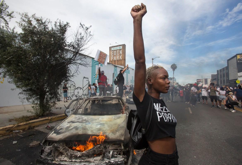 Demonstrantica pored zapaljenog policijskog vozila u Los Angelesu tokom protesta Black Lives Matter zbog ubistva Georgea Floyda. (AP)