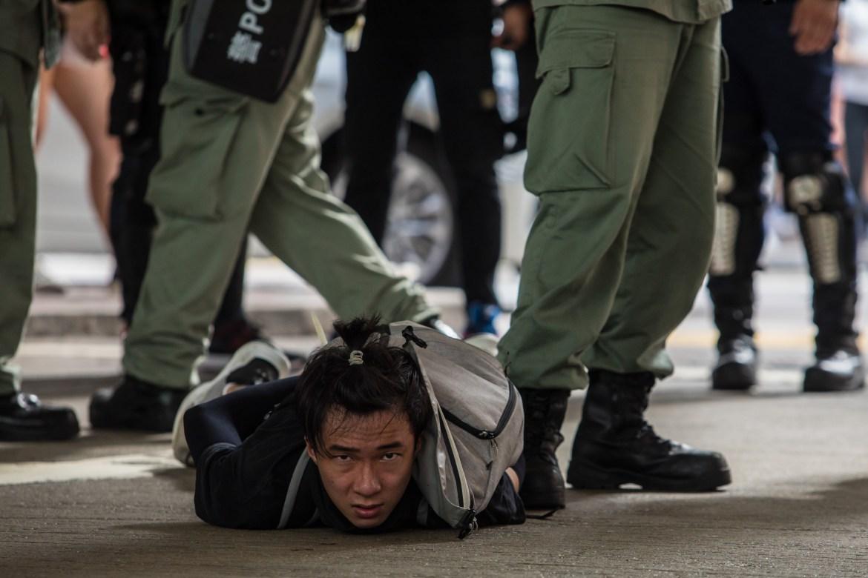 Čovjek koga je uhapsila policija za suzbijanje nemira tokom demonstracija u Hong Kongu. (AFP)