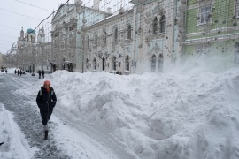 A woman walks past a heap of snow in Nikolskaya Street after heavy snowfall in central Moscow, Russia February 13, 2021. REUTERS/Shamil Zhumatov - RC2NRL9M1XM2