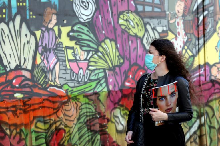 Žena na ulici u Sarajevu nosi masku na licu zbog pandemije korona virusa (EPA)