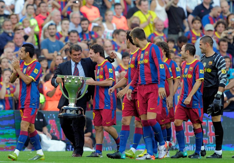 Predsjednik Barcelone Joan Laporta (drugi lijevo) i Messi drže španski prvoligaški trofej sezone 2009/10, sezonu prije prijateljske utakmice na stadionu Camp Nou u Barceloni 25. augusta 2010. [Albert Gea/Reuters]