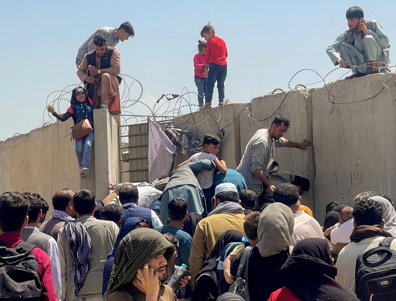 Afganistanci pokušavaju preskočiti zid na aerodromu (Reuters)